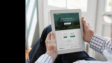 "Elderly man holding electronic tablet viewing ""Find a Medicare Plan"""